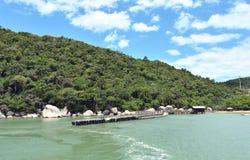 Um par na praia contra um monte verde e um céu azul Fotos de Stock