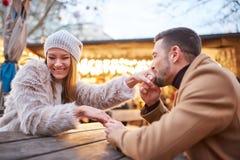 Um par nas mãos de beijo do amor em um mercado do Natal fotos de stock royalty free