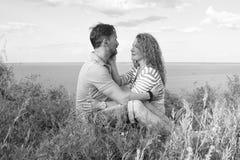 Um par no amor exterior O assento dos amantes abraçou na grama no banco do lago na grama no fundo da água e do céu imagem de stock