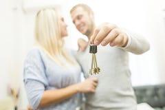 Um par novo bonito guarda na frente deles as chaves a seu apartamento novo imagens de stock royalty free