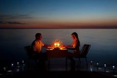 Um par novo compartilha de um comensal romântico com as velas na praia Fotos de Stock