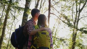 Um par novo de turistas aprecia uma caminhada nas madeiras no por do sol Estão, abraçam e olham para a frente Vista traseira video estoque