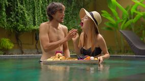 Um par novo de turistas da lua de mel tem seu próprio café da manhã pessoal em uma tabela de flutuação em uma piscina privada video estoque