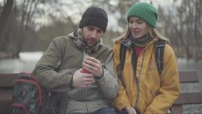 Um par novo de turistas que sentam-se no parque do banco na primavera O homem puxa uma garrafa t?rmica vermelha de uma trouxa fel video estoque