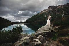 Um par novo do casamento aprecia um Mountain View na costa de um lago Morskie Oko foto de stock royalty free