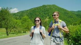 Um par novo do turista anda ao longo da estrada às montanhas bonitas cobertas com o modo de vida e as férias ativos da floresta vídeos de arquivo