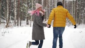 Um par novo e bonito está tendo o divertimento no parque, está correndo e está guardando as mãos O dia de Valentim e a história d video estoque