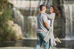 Um par novo está abraçando-se perto de uma cachoeira imagem de stock royalty free