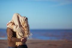 Um par novo está beijando sob o poncho de confecção de malhas da mulher Foto de Stock Royalty Free