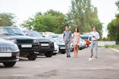 Um par novo está escolhendo um carro usado Tema do carro usado imagens de stock royalty free