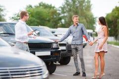Um par novo está escolhendo um carro usado Tema do carro usado imagem de stock