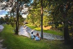 Um par novo nas meninas do amor que sentam-se no gramado pelo rio no dia ensolarado com o o seu de volta à lente na máscara do Fotos de Stock Royalty Free