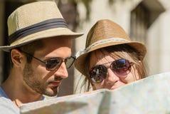 Um par novo, olhando um mapa Fotografia de Stock Royalty Free