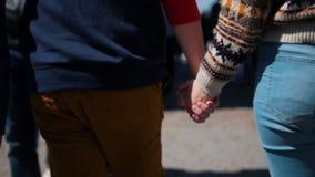 Um par novo que anda nas ruas que guardam as mãos em torno de uma multidão filme