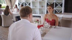 Um par novo que comunica-se em um restaurante do verão filme