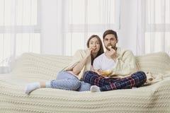 Um par novo que senta-se no sofá que olha uma tevê interessante imagem de stock royalty free