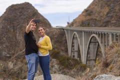 Um par novo toma um selfie no fron da ponte grande da angra, Big Sur, Califórnia, EUA fotos de stock royalty free