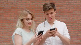 Um par novo usando telefones celulares fora fotos de stock royalty free