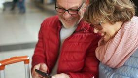 Um par pensionista estão sentando-se em um banco na estação de trem e estão olhando-se fotos de um quando do smartphone video estoque