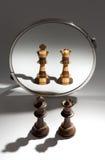 Um par preto de um rei e de uma rainha está olhando em um espelho para considerar-se como um par colorido preto e branco Fotos de Stock Royalty Free