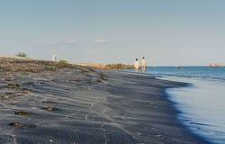 Um par que anda com os pés descalços na praia preta da areia Imagens de Stock