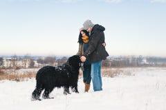 Um par que aprecia o inverno ao andar seu havin grande do cão preto imagens de stock royalty free