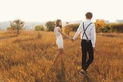 Um par que aprecia uma caminhada, guardando as mãos, com a cidade no ho fotografia de stock
