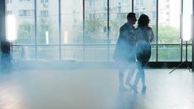 Um par que começa dançar quando fumar começa a aparecer vídeos de arquivo