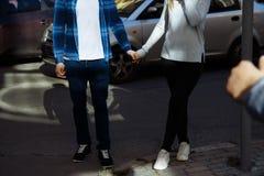 Um par que guarda as mãos e que cruza a estrada, andando em torno da cidade vista, amantes fotos de stock