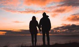 Um par que guarda as mãos no por do sol pelo mar fotos de stock