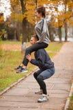 Um par que joga esportes em um parque do outono O indivíduo agacha-se guardando a menina em seus ombros fora fotografia de stock