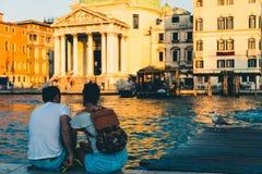 Um par que relaxa em um por do sol em Veneza, Itália imagens de stock royalty free