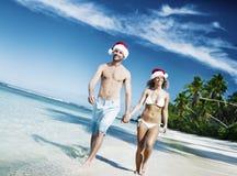 Um par que relaxa na praia no conceito do Natal imagens de stock