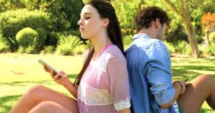 Um par que senta-se de volta ao smartphone traseiro e usando-se video estoque