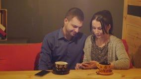 Um par que senta-se em um café, falando, bebe o café e a observação do telefone vídeos de arquivo