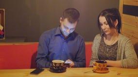 Um par que senta-se em um café, falando, bebe o café e a observação do telefone filme