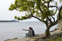 Um par que senta-se pelo lago foto de stock royalty free