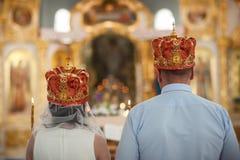 Um par recém-casados estão estando na frente do altar Vista da parte traseira Imagem de Stock Royalty Free