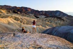 Um par relaxado de viajantes que apreciam a vista de montanhas corroídas antigas calmas ajardina no ponto de Zabriskie, o Vale da foto de stock royalty free