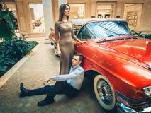 Um par romântico está estando pelo carro vermelho Clássicos americanos O indivíduo e a menina perto do carro vermelho Conceito id Imagem de Stock Royalty Free