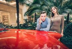Um par romântico está estando pelo carro vermelho Clássicos americanos O indivíduo e a menina perto do carro vermelho Conceito id Fotografia de Stock