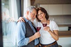 Um par superior com vinho dentro em casa, estando pela janela fotografia de stock royalty free