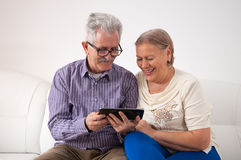 Um par superior feliz usando uma tabuleta digital Fotografia de Stock Royalty Free