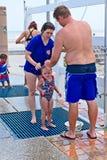 Um par tenta enxaguar fora sua criança em um chuveiro em uma praia exterior Foto de Stock