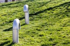 Um par tubulações do tubo de respiração do metal de uma reunião do metro em um parque público na grama verde imagens de stock