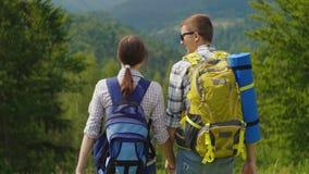 Um par turistas com trouxas incorporam o quadro Aprecie o cenário bonito da montanha Dia de verão claro vídeos de arquivo