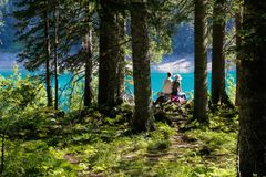 Um par turistas sentam-se em uma rocha na borda de um penhasco acima de um lago em uma floresta do pinho foto de stock