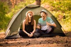 Um par turistas a tempo da caminhada, sentam-se e relaxam-se fora da barraca, admirando o cenário bonito da montanha imagem de stock