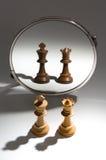 Um par um rei e uma rainha brancos estão olhando em um espelho para ver-se como um par preto Imagens de Stock