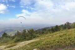 Um paraglider do voo contra o céu azul, na névoa da manhã das montanhas Carpathian Imagens de Stock